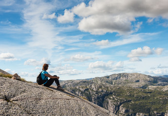 middle age hiker woman sitting on rock relaxing in Norway mountains