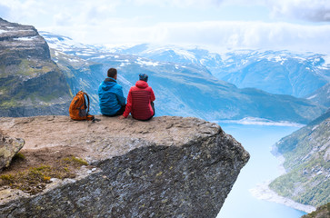 Couple sitting top view on the way to Trolltunga. Location: Scandinavian Mountains, Norway, Stavanger. Concept of freedom and success