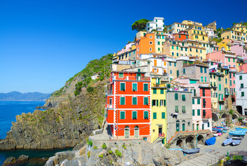 Riomaggiore traditional typical Italian fishing village in National park Cinque Terre, colorful multicolored buildings houses on hill, clear blue sky copy space background, La Spezia, Liguria, Italy