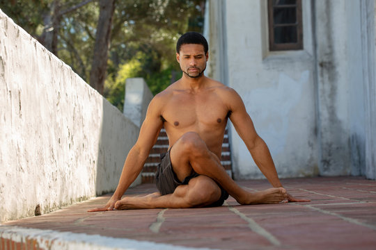 Male Yoga Instructor in Cross-Legged Seated Pose Looking Down