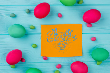 Happy Easter background with painted eggs. Colorful chicken eggs and candies on wooden plank. Easter greeting card.