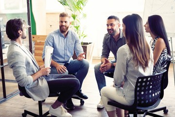 Teamwork is a key to success. Business people in smart casual wear talking and smiling while having a brainstorm meeting in office. Wall mural