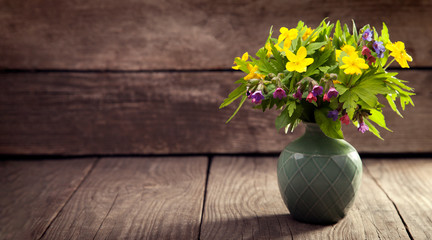 bouquet of field wild flowers in a vase on old boards