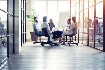 Teamwork is a key to success. Business people in smart casual wear talking and smiling while having a brainstorm meeting in office.