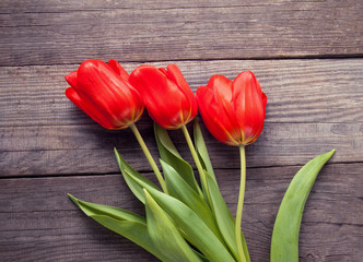 Red tulips on old wooden grunge boards top view