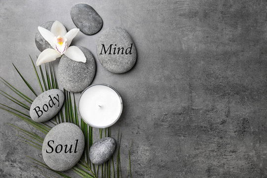 Spa stones and beautiful flower on grey background