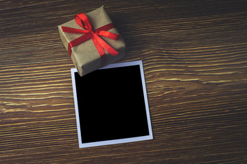 An empty photo is on a wooden table next to the gift box