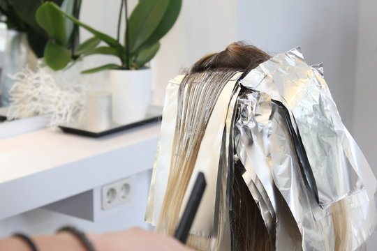 Balayage Trendstyle bei junger Frau blonden Haaren, Farbe wird augetragen, kühles blond