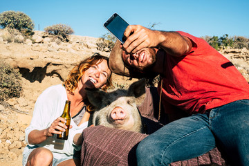 Alternative family or friends with young man and woman smiling while take a selfie with a domestic pig in the middle - everybody smile for the camera - sunny day and unusual use of phone technology