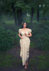 A mysterious princess in a white vintage dress lost in a fairytale enchanted forest. Long, black hair adorns the golden wreath. Emotions of fear and curiosity. Art photo