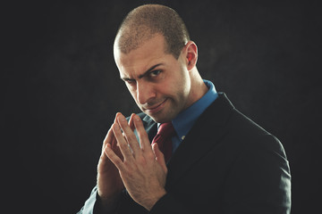 Unscrupolous businessman portrait in a dark background