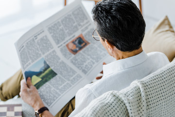selective focus of man reading newspaper at home