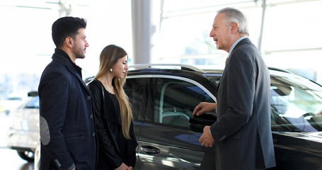 Car dealer showing a car to a couple