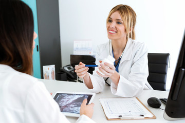 Pretty young woman gynecologist doctor prescribing medication for pregnant in the medical consultation.