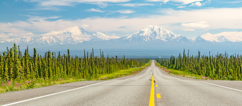 Alaska Range mountains on horizon at the end of long highway with green trees on side of highway. Yellow line in middle of highway in Alaska, USA.