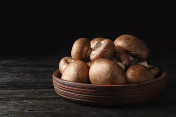 Bowl with fresh champignon mushrooms on wooden table. Space for text