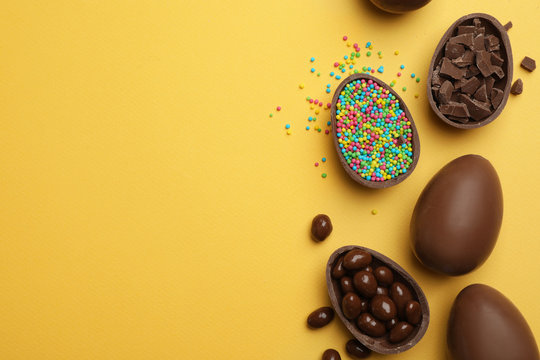 Tasty chocolate Easter eggs on color background, flat lay with space for text