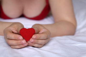 Declaration of love, woman holding red knitted heart in hands. Sexy girl in red bra lying on the bed, concept of Valentines day, motherhood, health care, romantic sex or blood donation