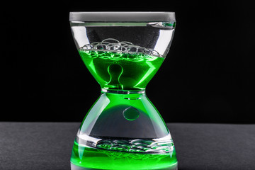 liquid hourglass made of water and oil, on dark background