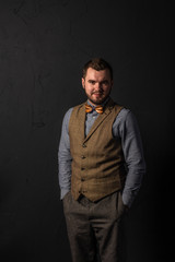 Stylish young man in wooden bowtie. Business style. Fashionable image. Office worker. Sexy man standing and looking at the camera