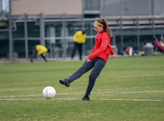 Young high school girl competing in a soccer match