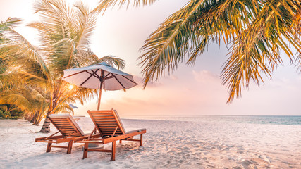 Wall Mural - Tropical beach resort hotel background as summer landscape with lounge chairs and palm trees in sun rays and calm sea for beach banner. Luxury vacation and holiday destination concept