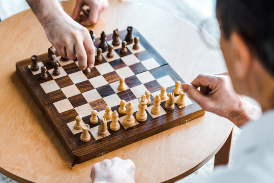 selective focus of wooden chess board with retired men playing chess at home