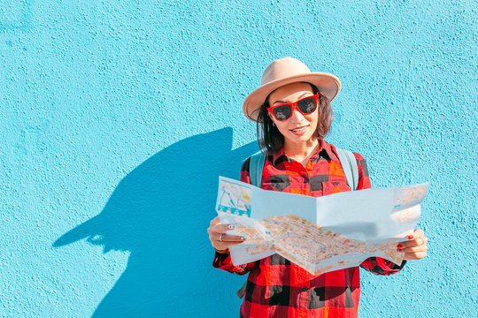 a young happy asian girl in a hat travels with a map in Burano, Venice