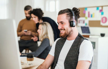 Young businessman with headphones and colleagues in a modern office.