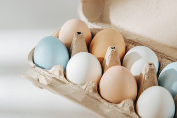 Natural Colored brown and white Eggs in egg box with sunlights.. Compositions in pastel colors. Easter consept.