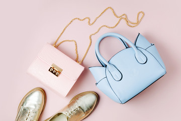 Fashion handbags with shoes on pale pink background. Flat lay, top view. Spring/summer fashion concept in pastel colored