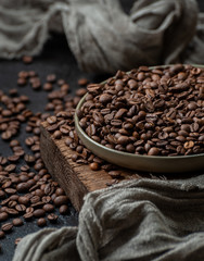 Freshly roasted coffee beans on a dark table in vintage style. Low key photography.