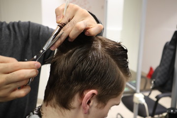 master hairdresser does hairstyle and style with scissors and comb. Master stacks hair of men in barbershop, hairdresser makes hairstyle for young man. Barber shop. Light