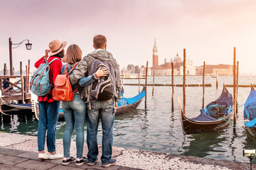 Foto op Aluminium Gondolas Group of happy friends travelers having fun on San Marco Square with gondolas and Grand channel at the background in Venice. Vacation and holidays in Italy and Europe concept