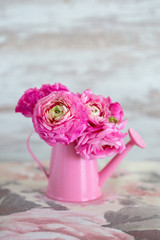 Close-up floral composition with a pink Ranunculus flowers in a vase. Beautiful bouquet of spring flowers.