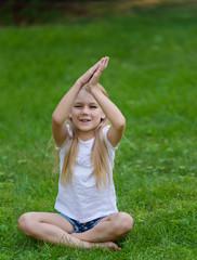 Little girl outdoor on the fresh grass meditates