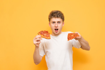 Amazed young man on a yellow background,holding two pieces of pizza in his hands and looking into the camera.Emotional man eats a pizza,looks at the camera in amazement,isolated on a yellow background