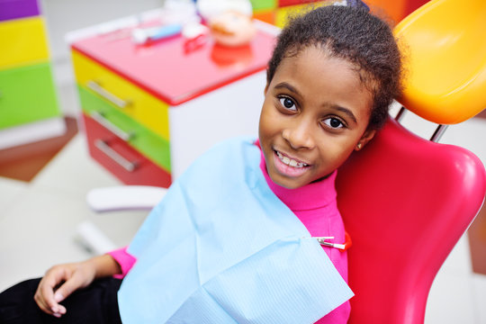 cute black baby girl smiling sitting in a red dental chair at the examination at the children's dentist