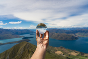 holding a lens ball at the top of Roys peak in New Zealand, crystal ball on the top of a mountain in New Zealand, Roys peak image, lens ball photography
