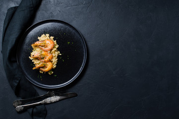 Italian risotto with shrimp on a black plate. Dark background, top view, space for text