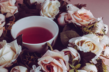 Tea with pink and white roses on a pink background
