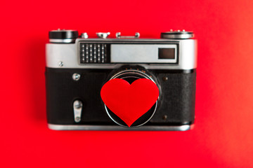 old vintage photo camera with red heart on it. red background.for decor and design. valentines greeting card. concept love and romance at photographs.