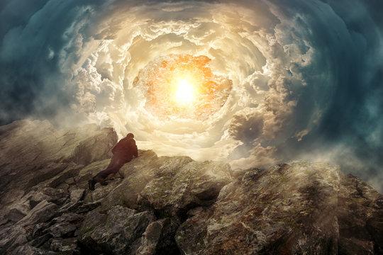 Mann auf einem Felsengipfel schaut in einen surrealen Wolkentunnel