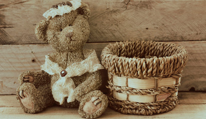 vintage bear sitting next to a woven basket on a wood background with writing space perfect for greeting card