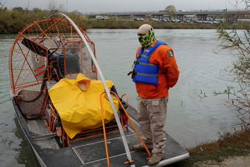 A member of the Mexican immigrant welfare agency Grupo Beta takes a break in the banks of Rio Bravo as a formation of U.S. security cars can be seen on the other side of the river, Piedras Negras, Mexico