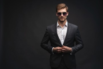 Stylish young man in suit and sunglasses. Business style. Office worker. Sexy man standing isolated over gray background