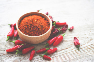 Red chili pepper and ground dry hot spice in a wooden bowl on a wooden old background,  top view
