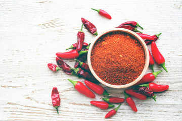 Red chili pepper and spices in wooden bowl on wooden old background