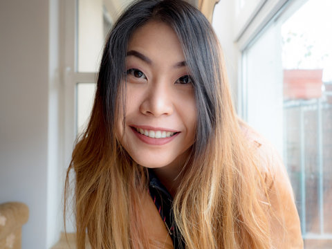 A portrait of excited Asian young woman sitting at home and looking at camera with joy, happy face. Adorable lady glad to see friend, family making video call by Internet.