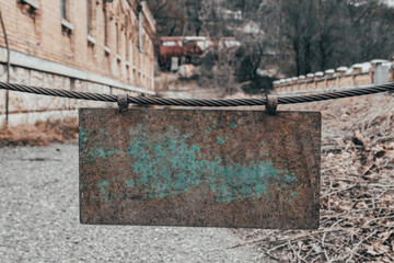 Old abandoned sign on the iron rope that blocks the road